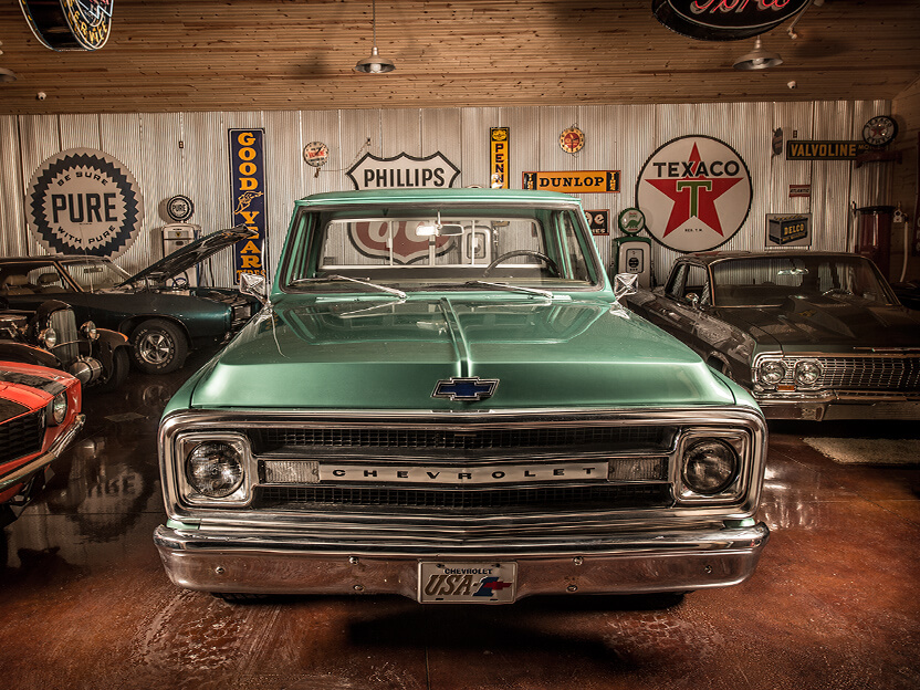A green collectible car parked in a garage with other collectible vehicles and vintage signs.