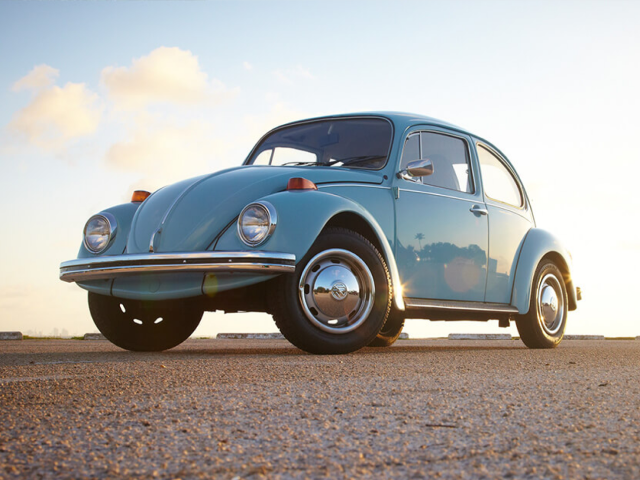 A sky blue collector Volkswagen Beetle parked on concrete, with blue sky in the background.