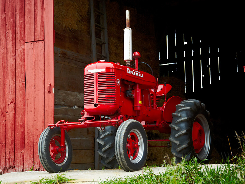 A red collector tractor in front of a red barn.