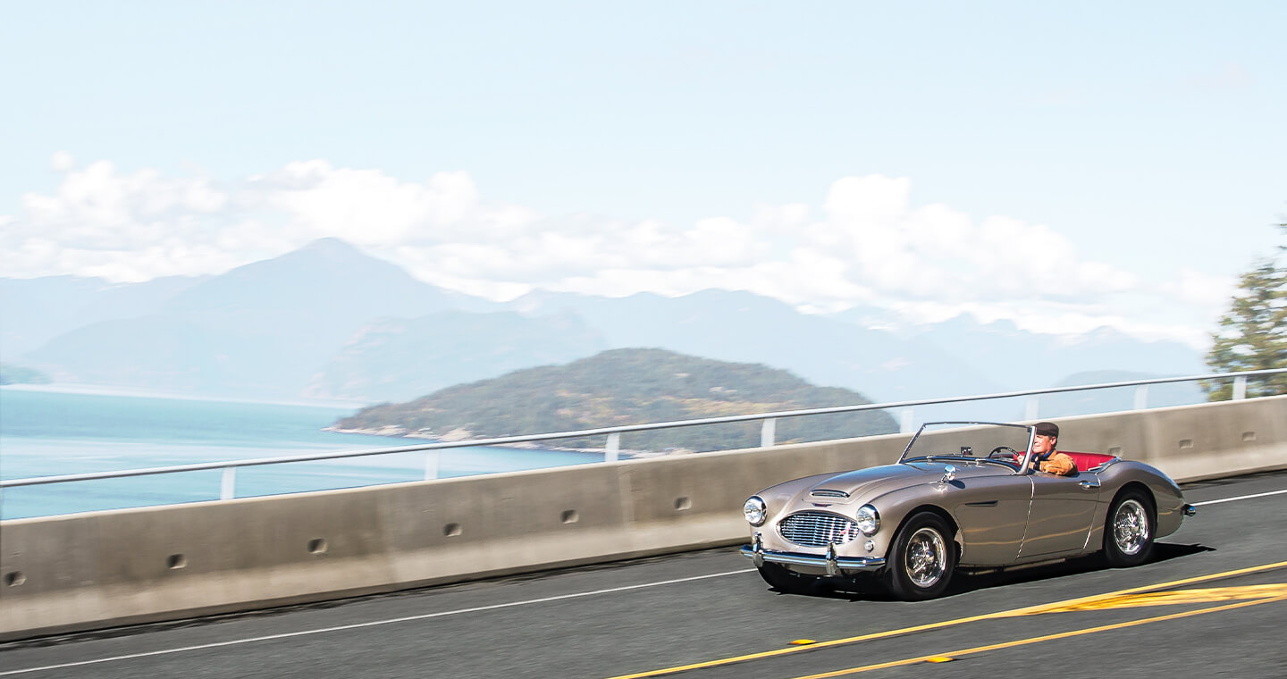 A collector convertible, driving on a freeway with mountains in the background.