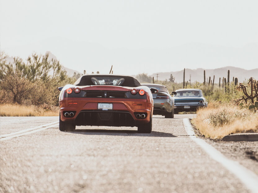 Three collector cars driving down a desert road with mountains in the background.