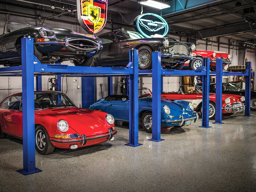 Rare and high value collector vehicles showcased in a garage.