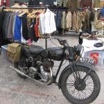 Royal Enfield motorcycle and vintage clothing stand.