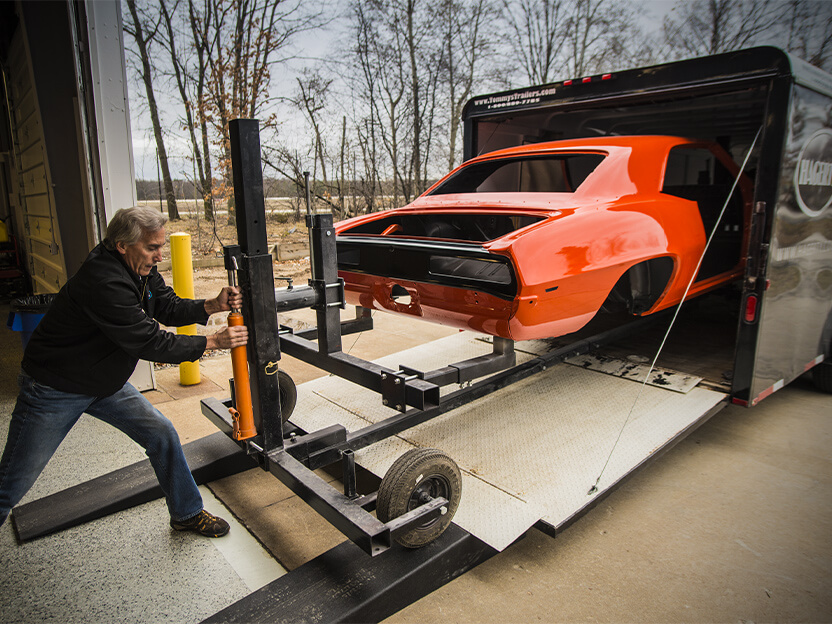 An orangish red collector vehiclebeing pulled from a trailer.