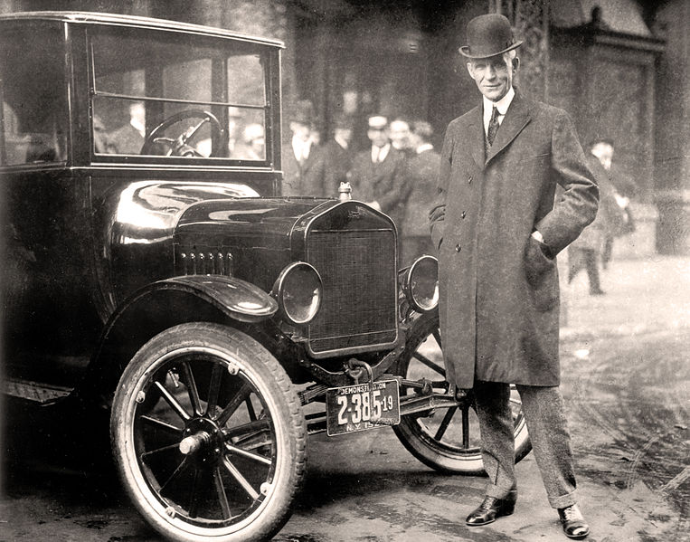 Henry Ford standing next to a Model T in 1921