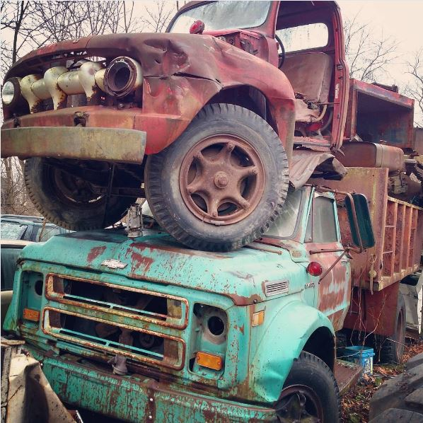old Ford pickup stacked atop a Chevy dump truck