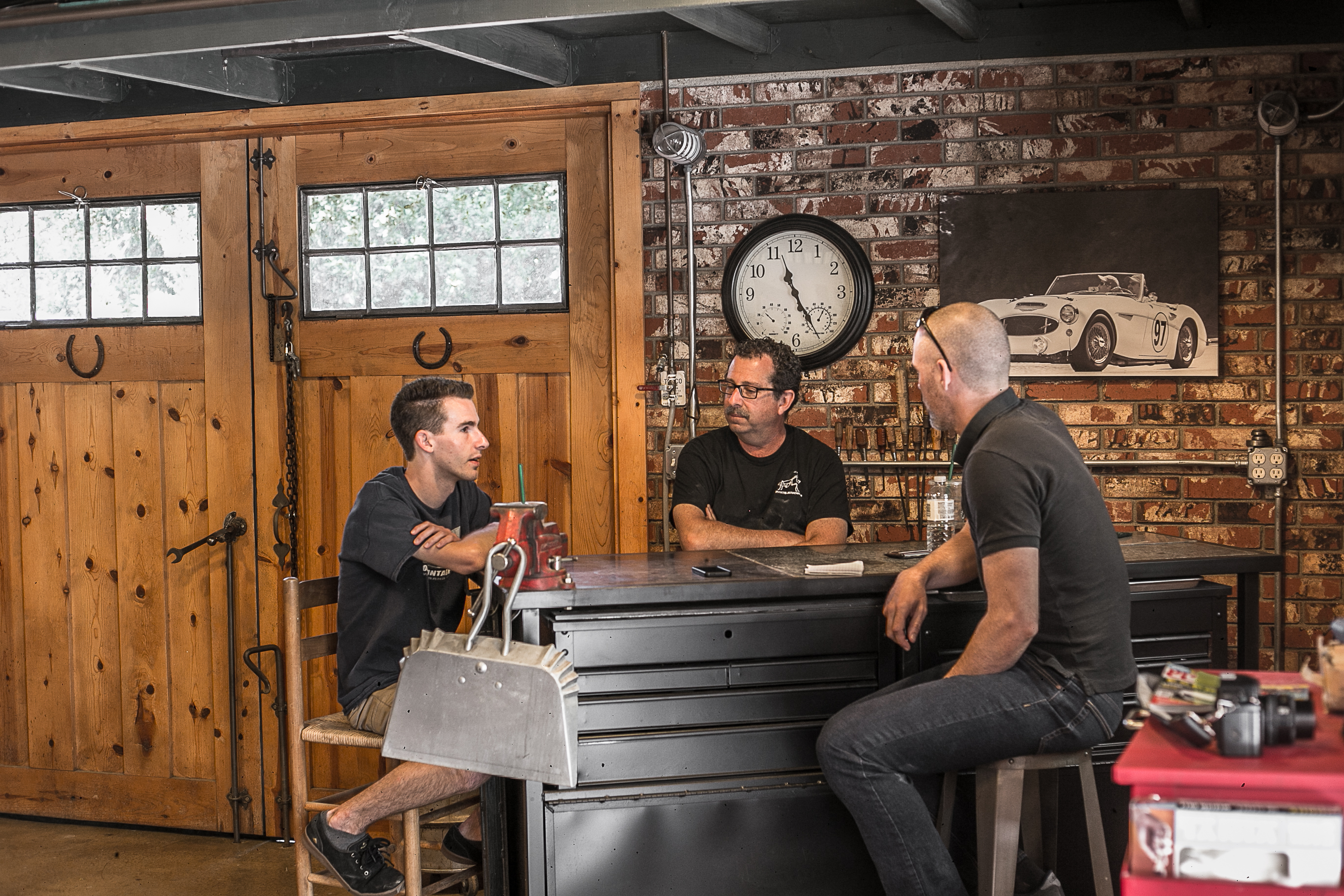 Dean Caccavo (center) and son Austin (left) chat with writer Aaron McKenzie in their Thousand Oaks, California, garage.