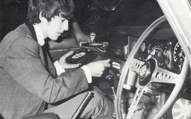 George Harrison shows off the Philips Auto Mignon turntable in his 1965 Jaguar XKE.