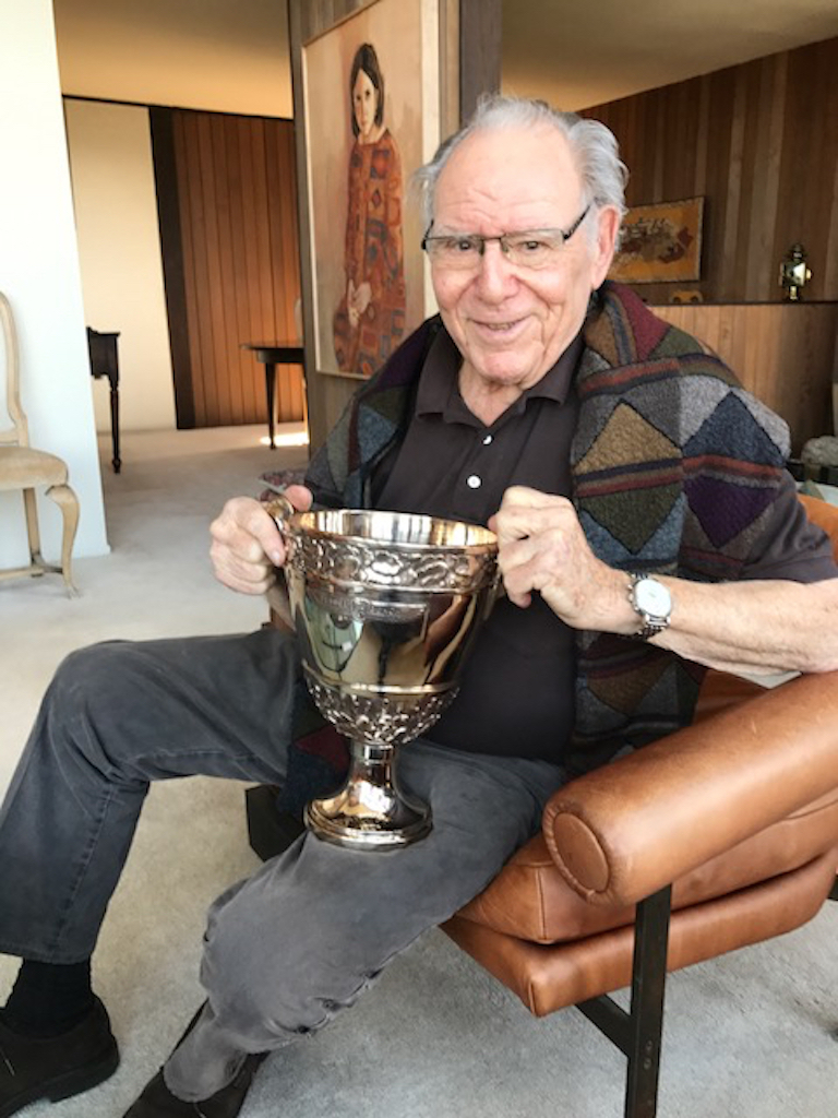Jules Heumann holding the Pebble Beach Concours d'Elegance 'Best in Show' trophy