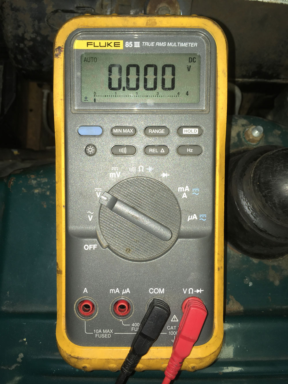 """A multimeter configured to measure voltage (red probe in the """"VR"""" socket, rotary dial turned to DC voltage setting)."""