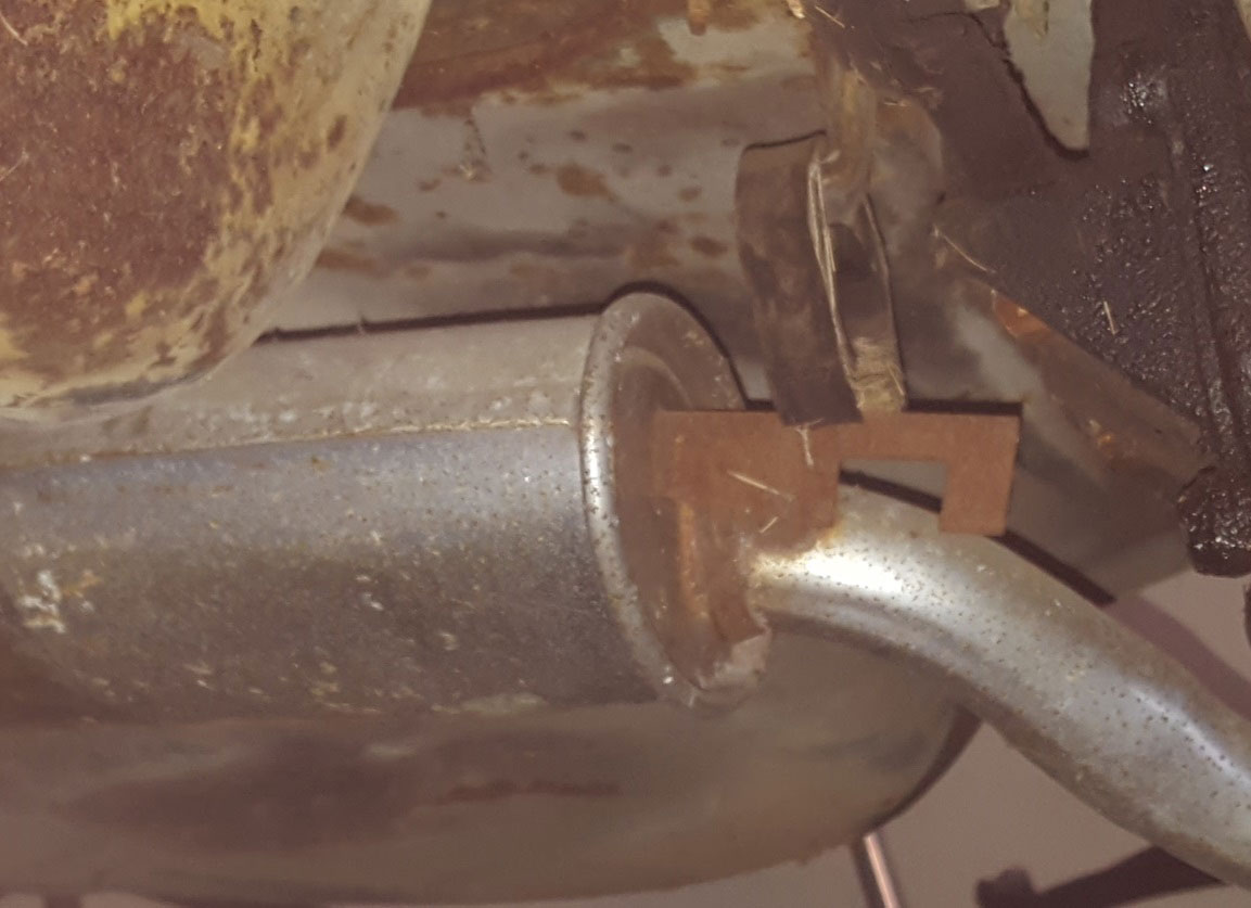 This rubber exhaust hanger has worn through, which will leave the exhaust banging.