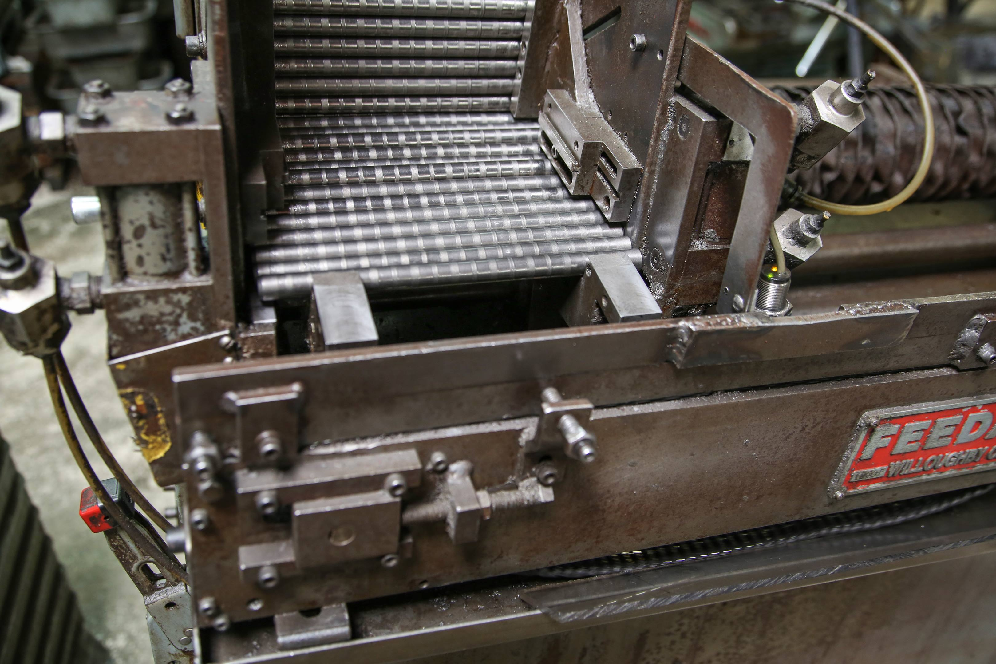 Studs are loaded into a grinding machine. Notice the perpendicular marks on the shank of the studs left by the straightening roller.