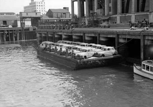 A barge loaded with 22 Austin A40 cars that were damaged by fire and salt water is set to be towed into Vancouver's English Bay on May 9, 1952.