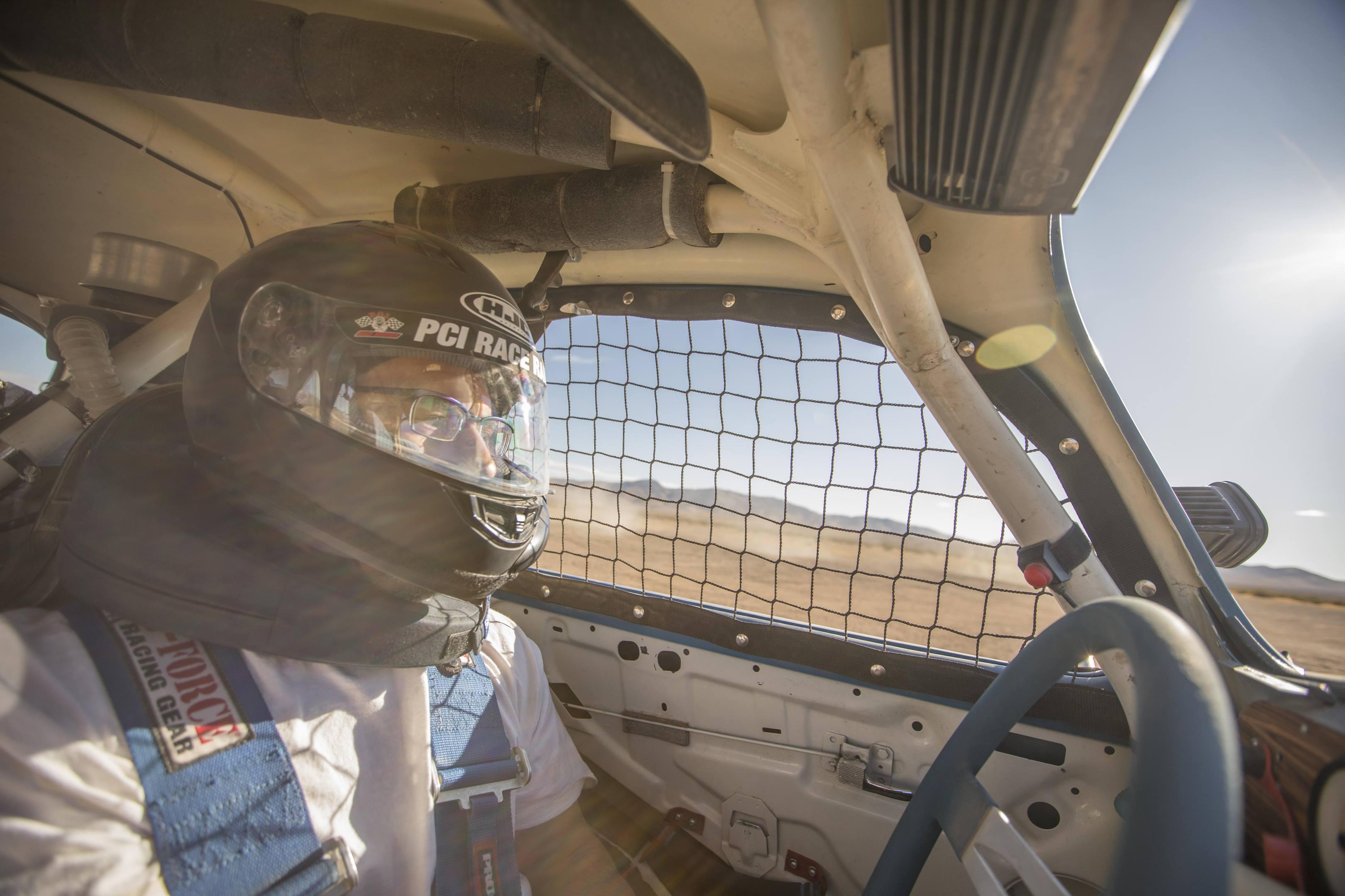 Aaron Robinson behind the wheel of a BAJA Beetle in the desert