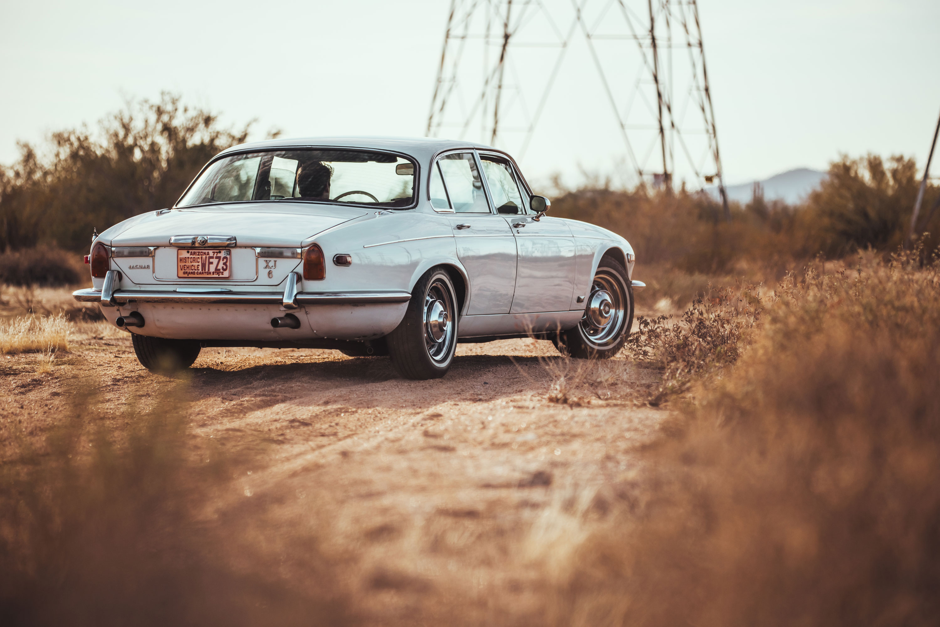 1974 Jaguar XJ6 driving away in the desert