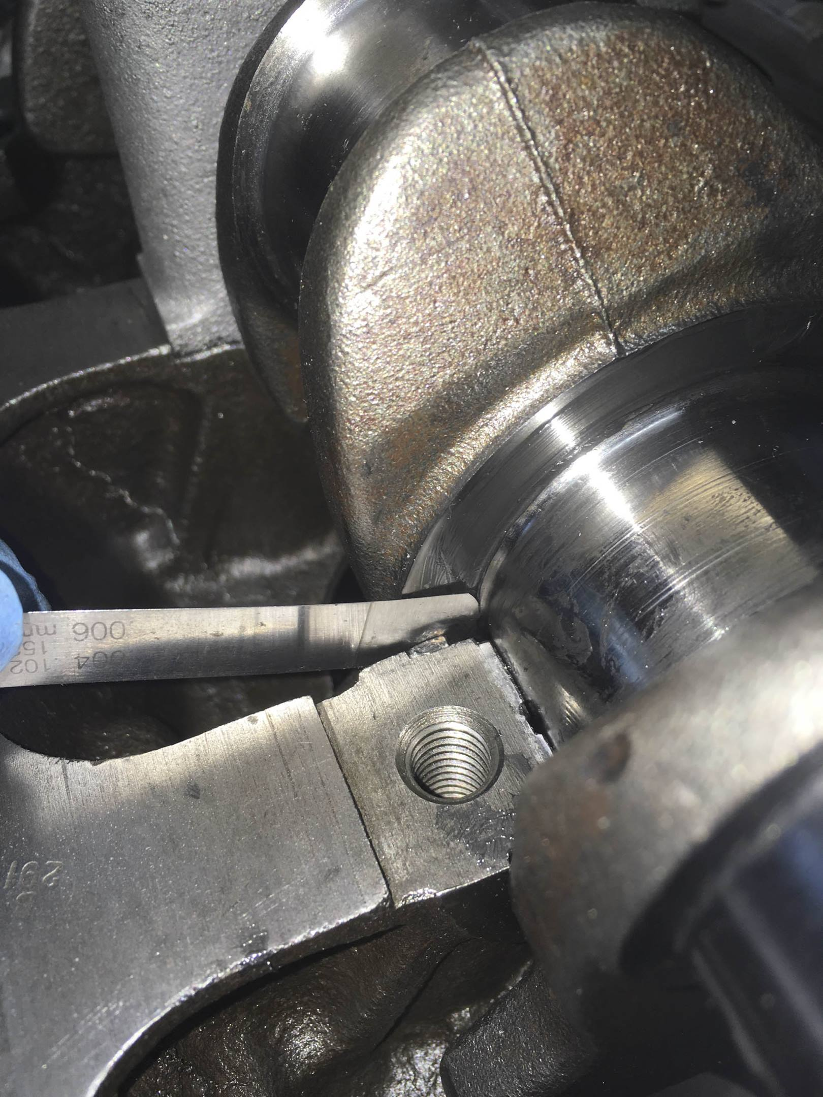 A first cut at measuring crankshaft float with a feeler gauge between the thrust washer and crankshaft thrust surface. Light score marks described above are clearly visible although the journal face is actually smooth and polished.