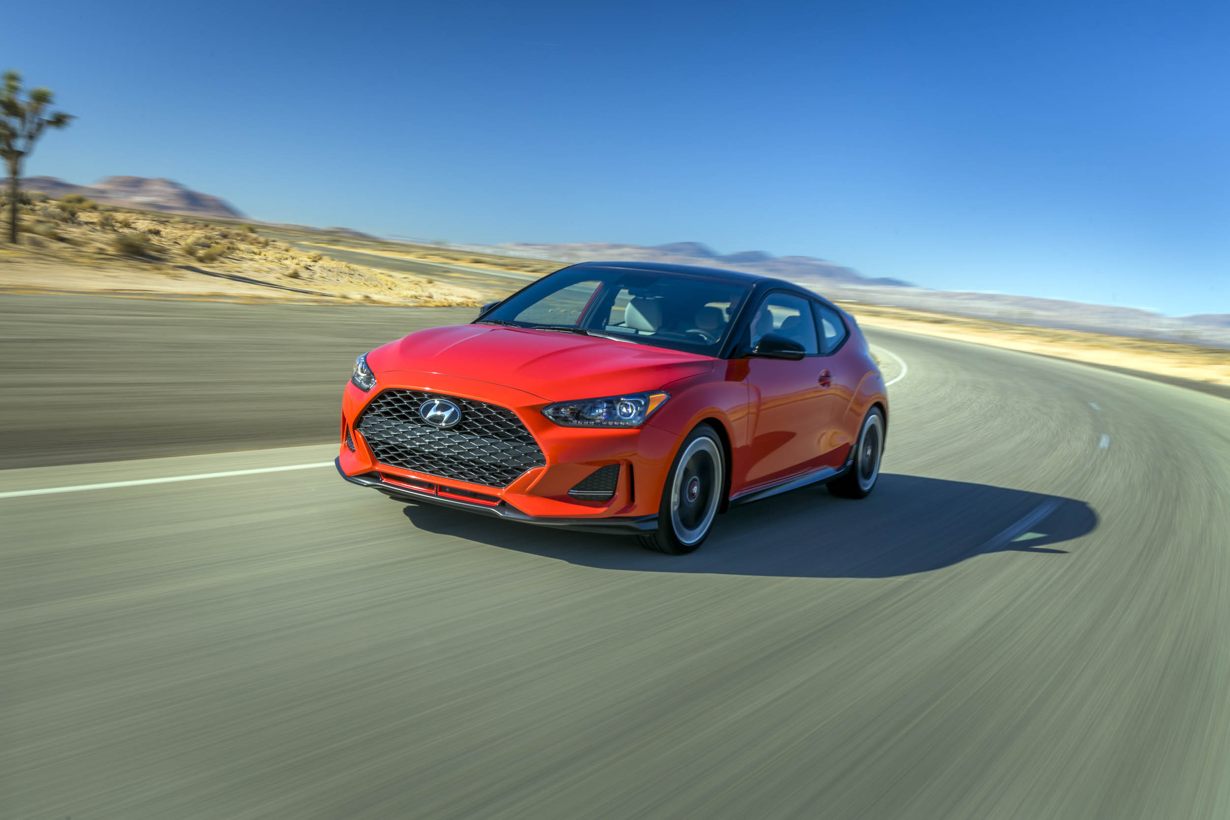 Red 2019 Hyundai Veloster front 3/4 on the road