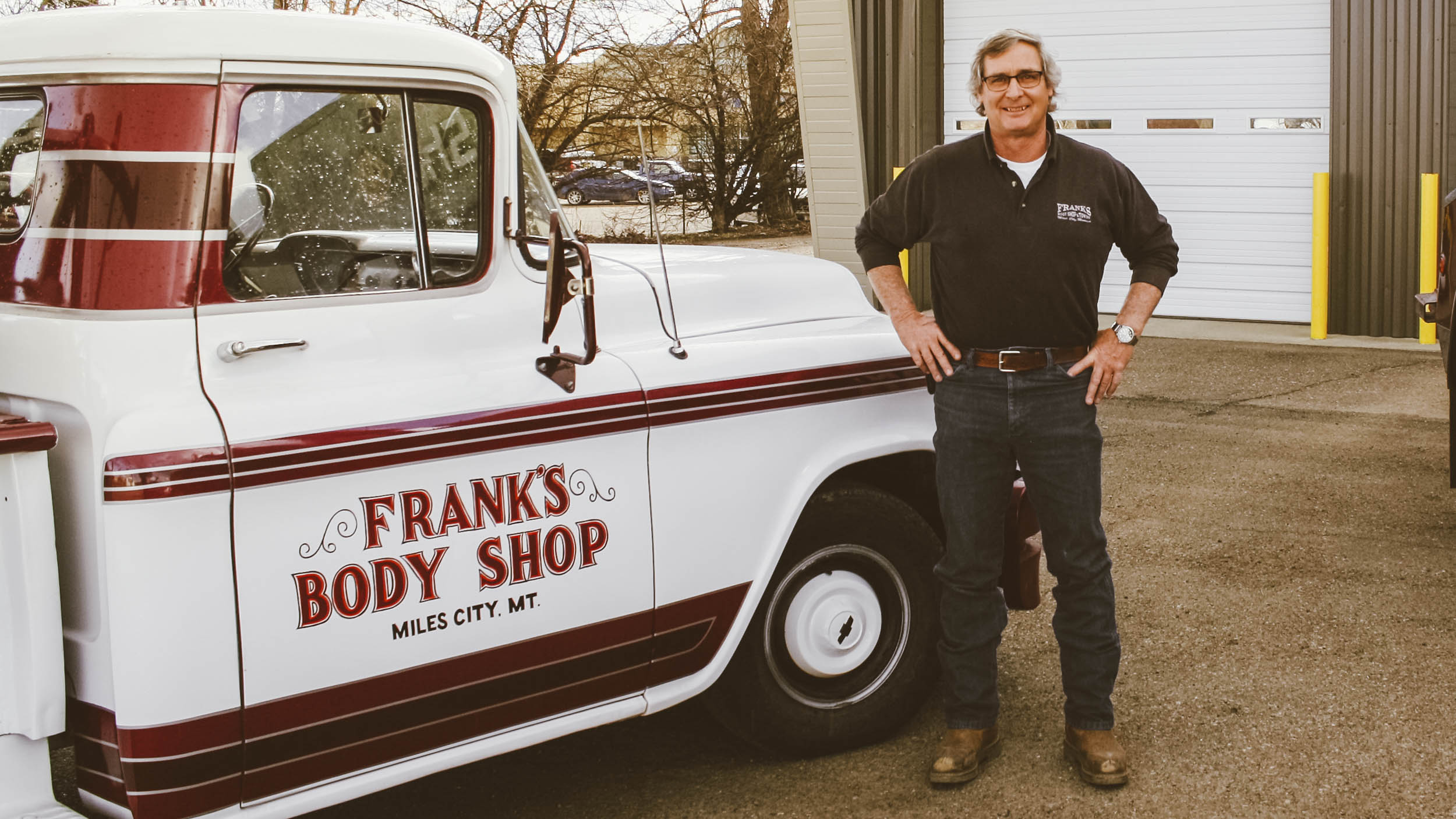 Tim Stoltz, who's been working in the body repair and towing business for 45 years, stands between the truck he started in when he was a boy and one of the five newer trucks his shop uses on a daily basis.