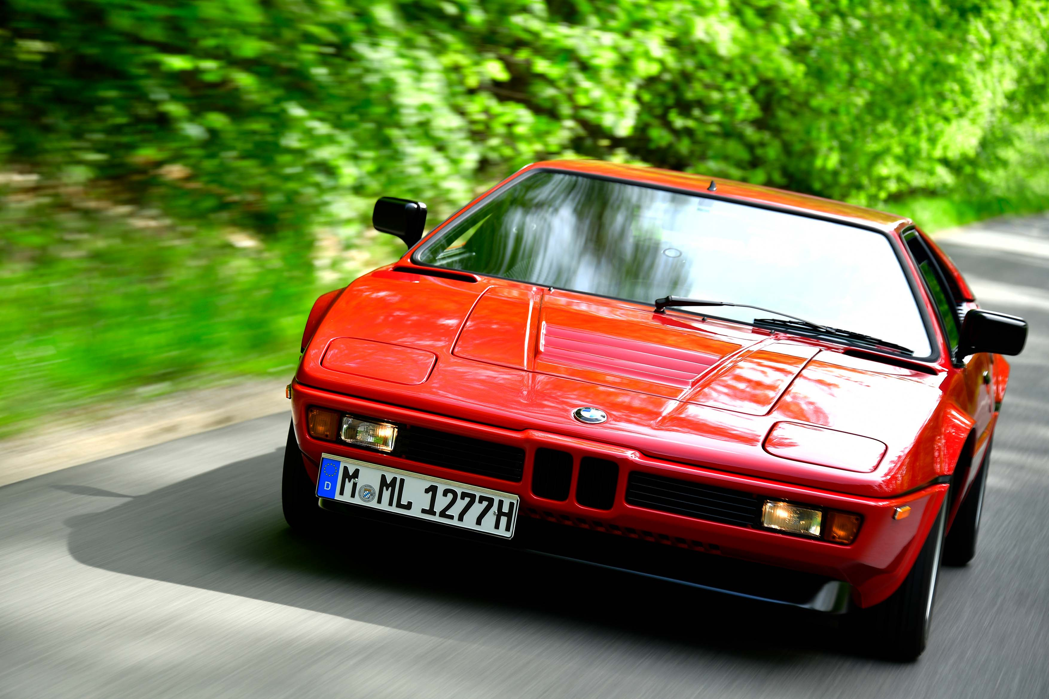 BMW M1 on road green trees background