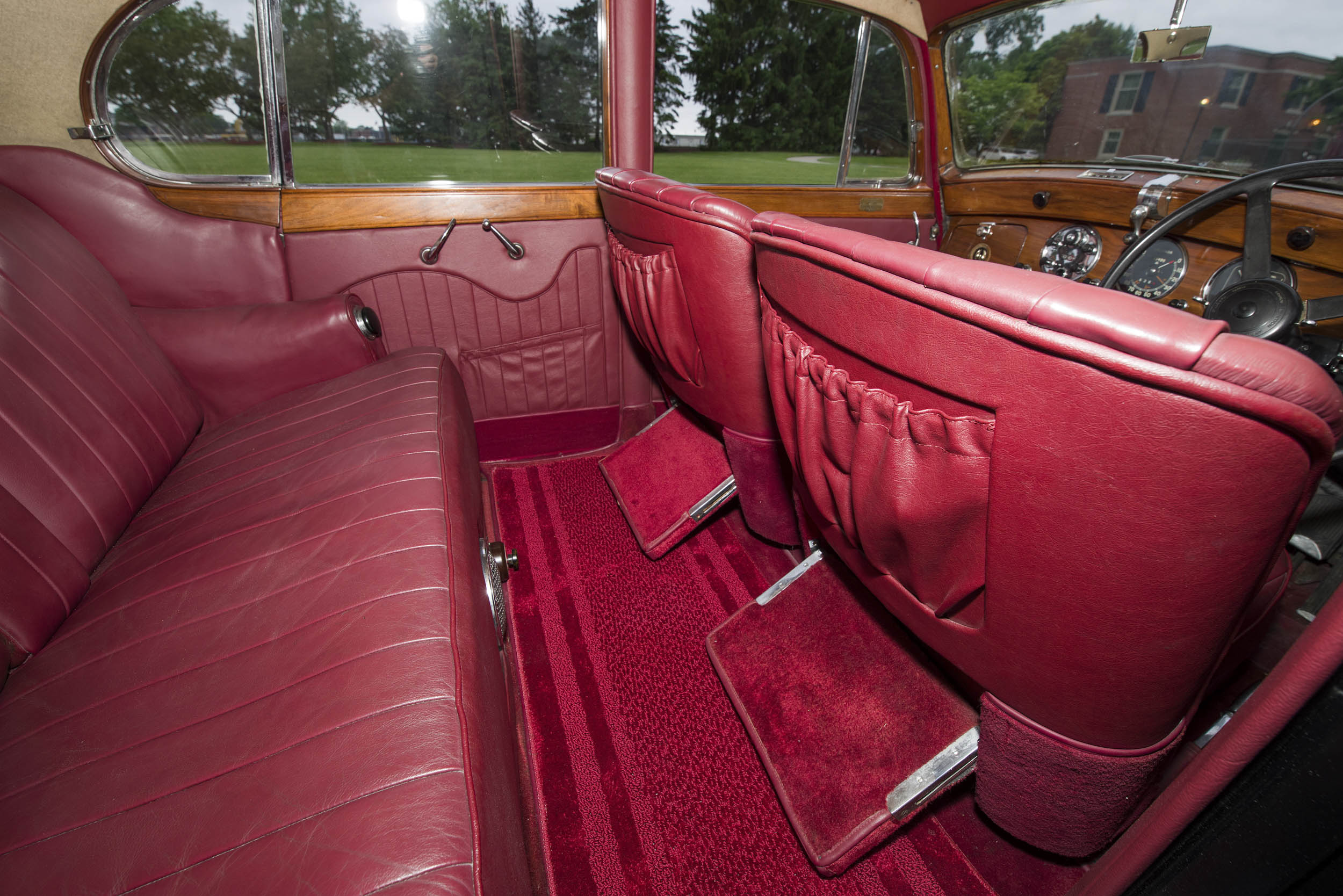 The cabin is upholstered in red leather. Pulldown footrests and stowage bins are provided for the comfort and convenience of rear-seat passengers.