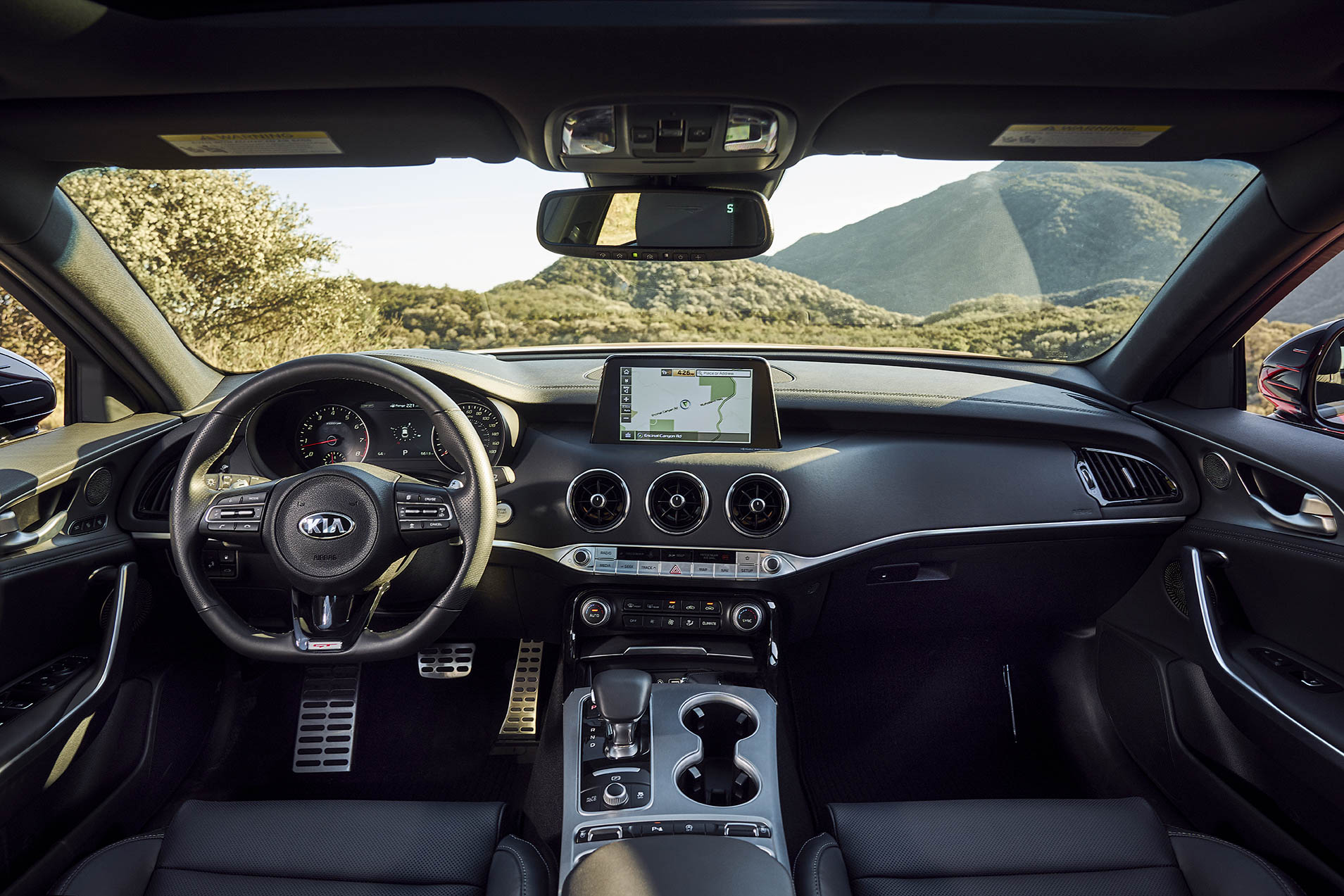 All is modern in the new Kia, with the requisite display screen and banks of buttons. But as you can see, circular dials and vents still convey sportiness, even after 50 years.