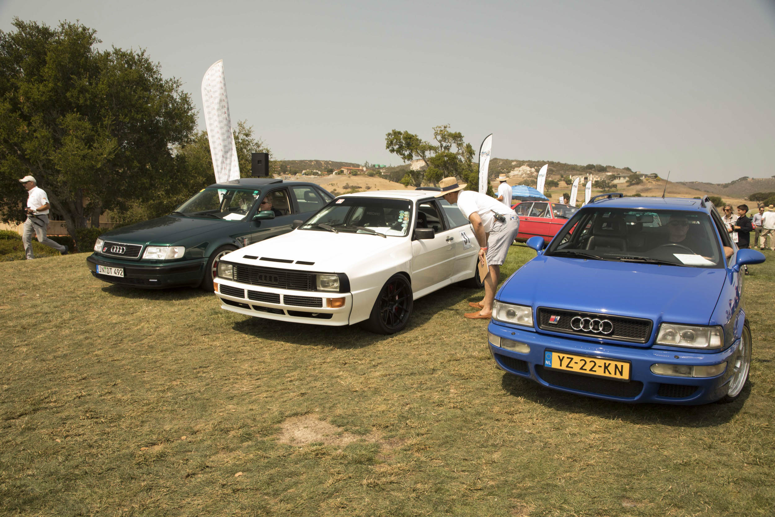 "Significant Audis were thin on the ground at Legends, but these three are blue-chip collectibles: At left is a green S4 Avant, aka ""Ur-S4."" The white car is a 1983 Sport Quattro, or ""Ur-Quattro,"" with many powertrain, suspension, and bodywork modifications, including a 20-valve five-cylinder engine; it's owned by Dean Treadway. And the blue wagon is an RS2 Avant, the first RS Audi ever built. Like the Mercedes 500E, it was assembled by Porsche, for a very limited run in 1994–95."