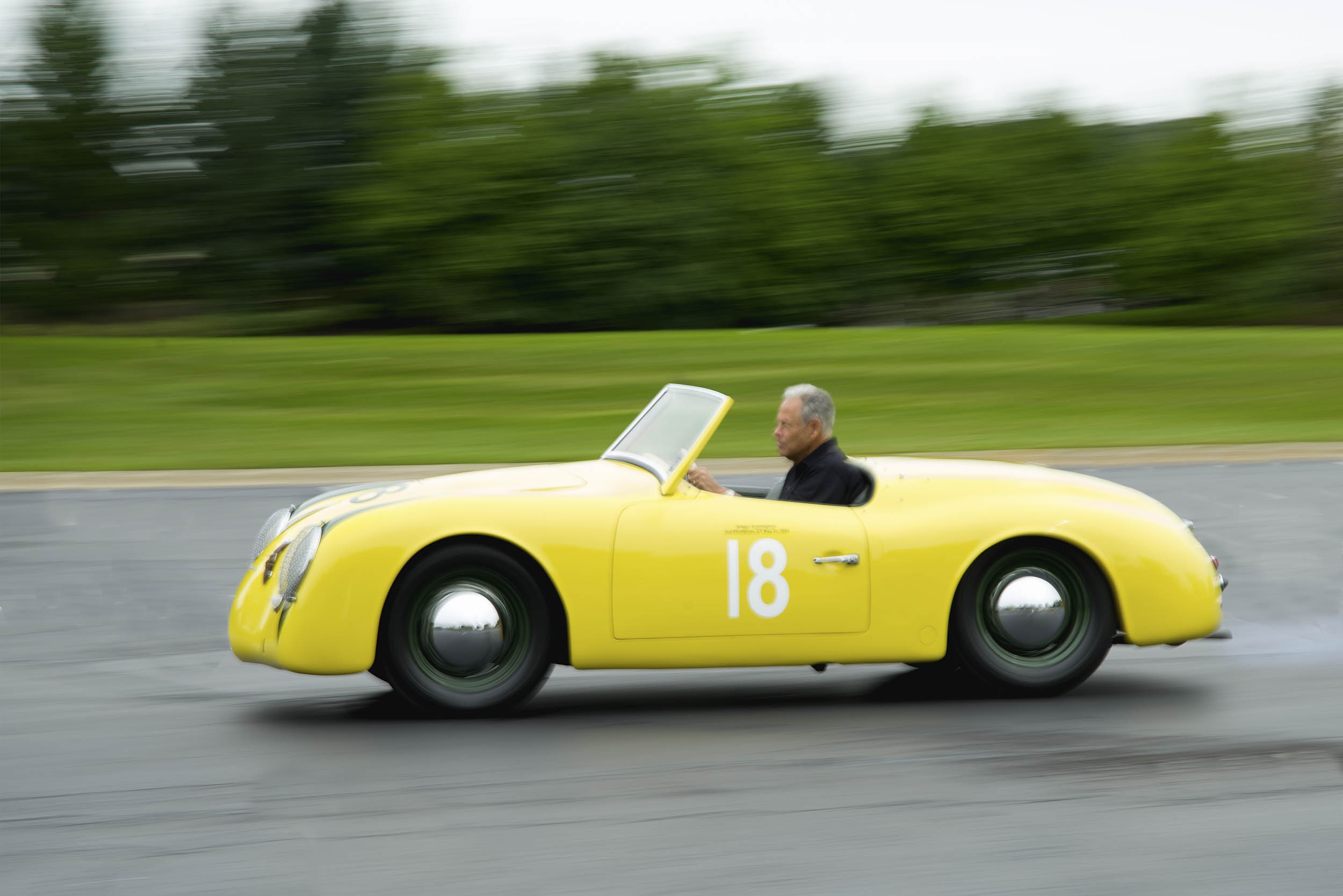 Rev. Ronald Roland drives his Porsche in the parking lot of the Inn at St. John's in Plymouth, Michigan. At a mere 1581 pounds, the car's 75-horsepower boxer four renders it a responsive ride. When Brigg's Cunningham Jr. drove the car in competition, it wore number 18.