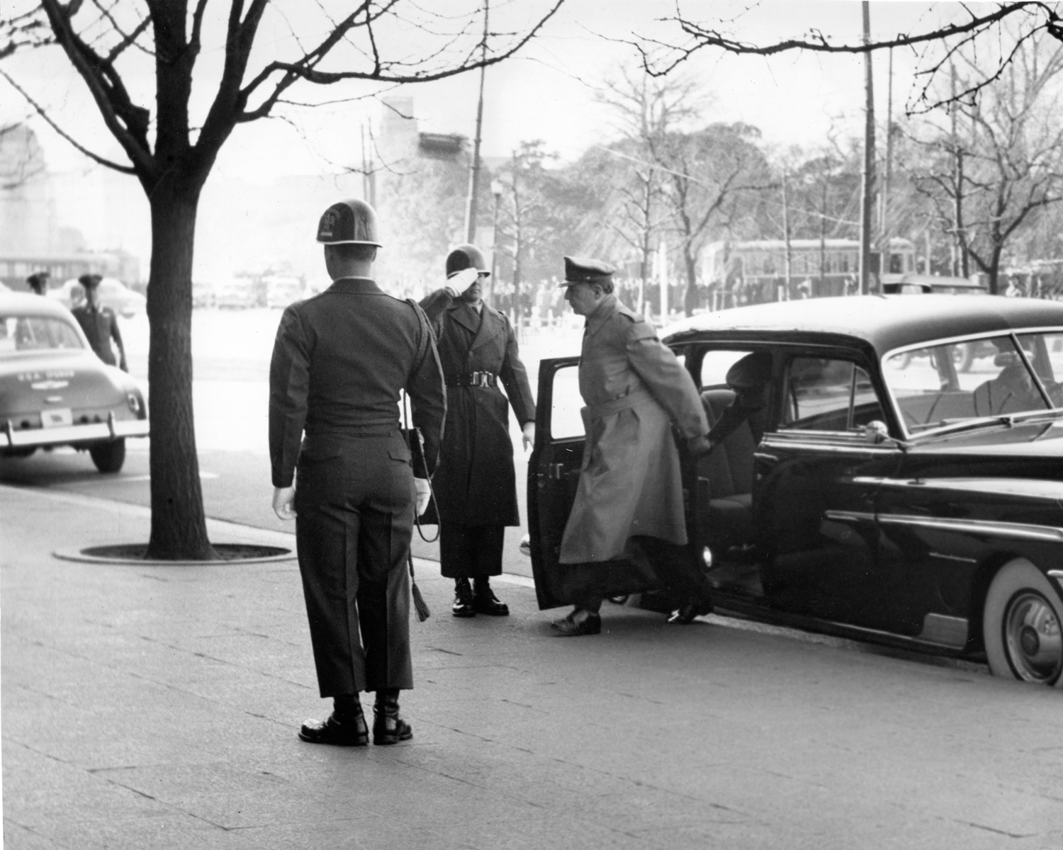 MacArthur arrives at his office on his 71st birthday at the General Headquarters of the Far East Command in his 1950 Chrysler Crown Imperial limousine.
