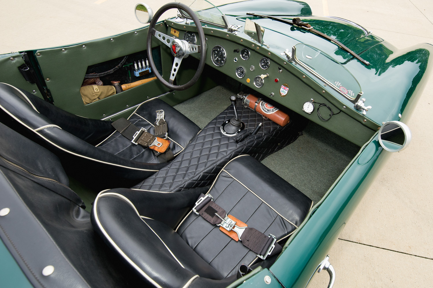 The upholstery is as it was when the car was raced in England during the 1970s. A cavity inside the driver's door holds spare spark plugs, a wrench for the hood locks, and a brass hammer for wheel knockoff removal.