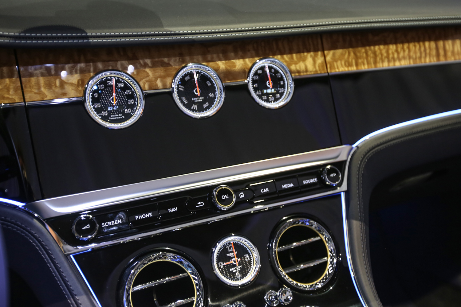 Bentley gives driver two different options for the center stack when driving, one digital, the other analog. wood dash