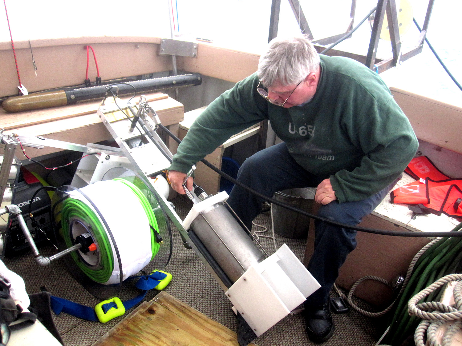 "Jerry Eliason, the electronics expert on the discovery team, makes final adjustments to the sonar ""fish"" that will be towed in deep water behind the boat."