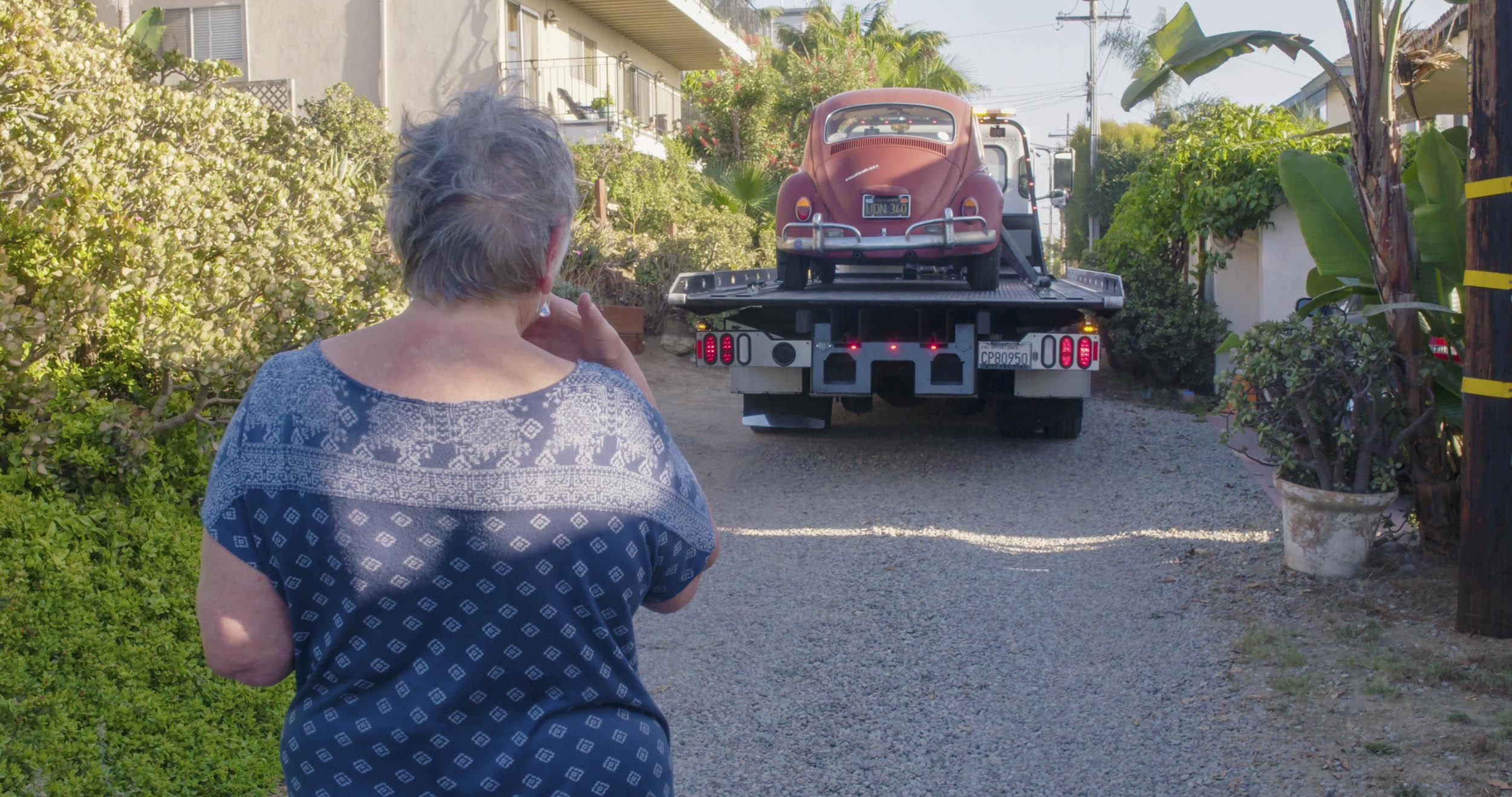 Annie watching her 1967 Volkswagen Beetle being taken away