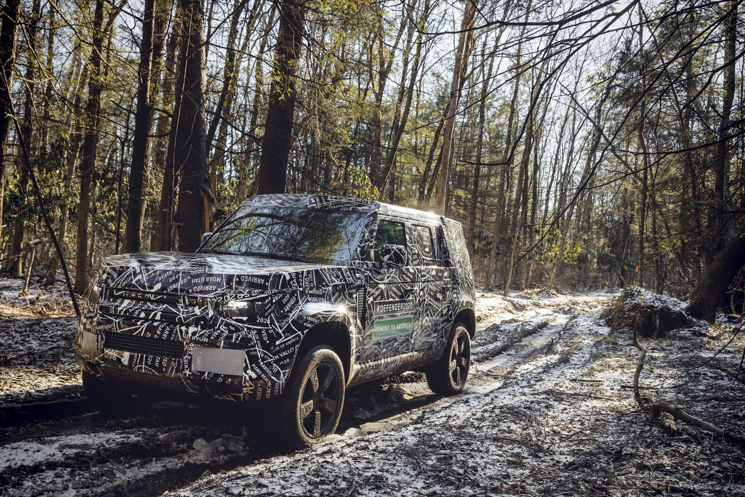 2020 Land Rover Defender driving through the woods