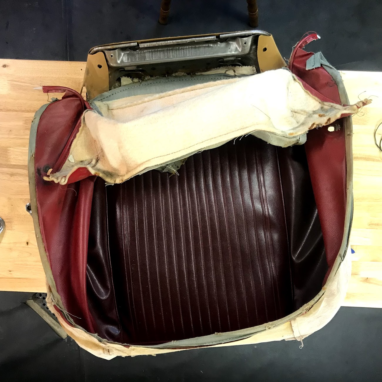 An example of how dark the bright red vinyl had faded. It might have been possible to clean this seat bottom, but with the other damage it made sense to replace it.