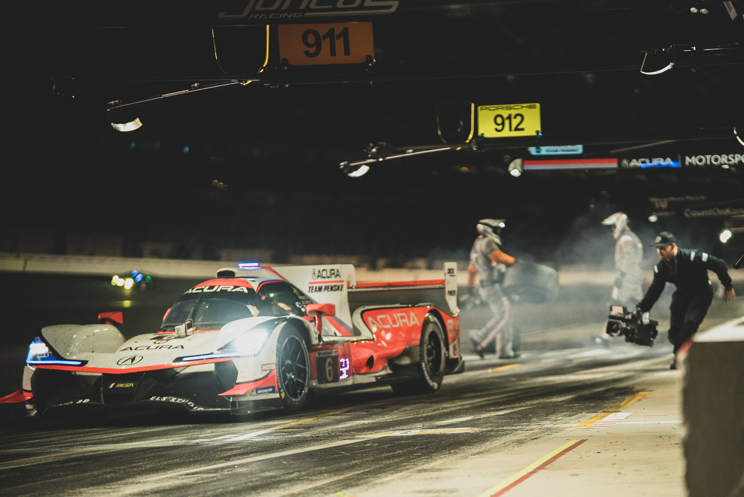 TV crews also took shifts chasing cars throughout the night. One lucky crew member chases down an Acura DPi on pit lane.