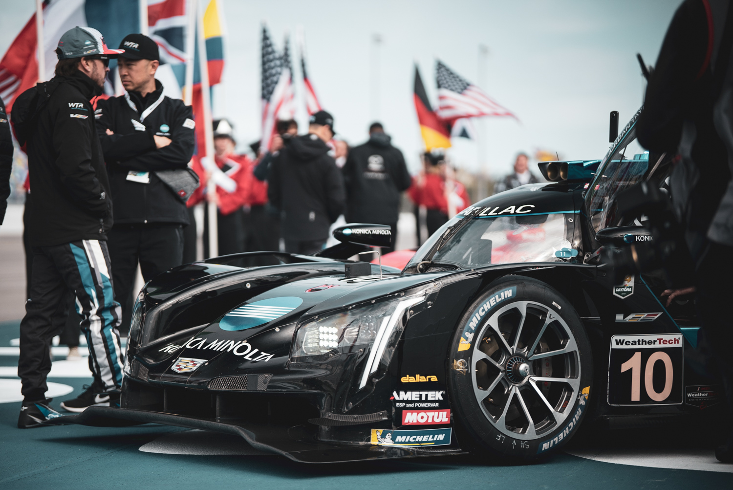 The eventual race-winner, Wayne Taylor Racing, sits idle on the grid. Alonso (far left) walks around the front fender of the car that he eventually piloted to victory.