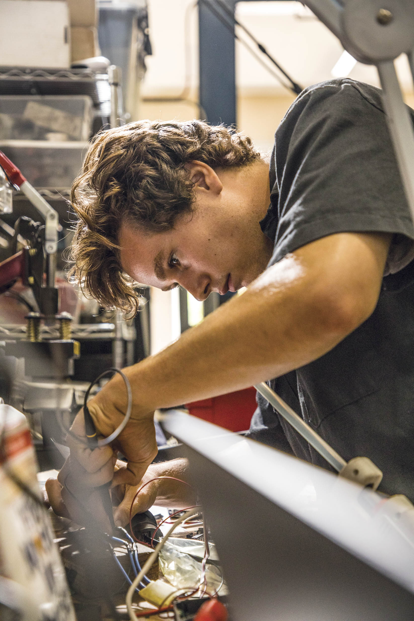 Milo Darling works on a control system at the EV West shop in San Marcos, which specializes in electric conversions.