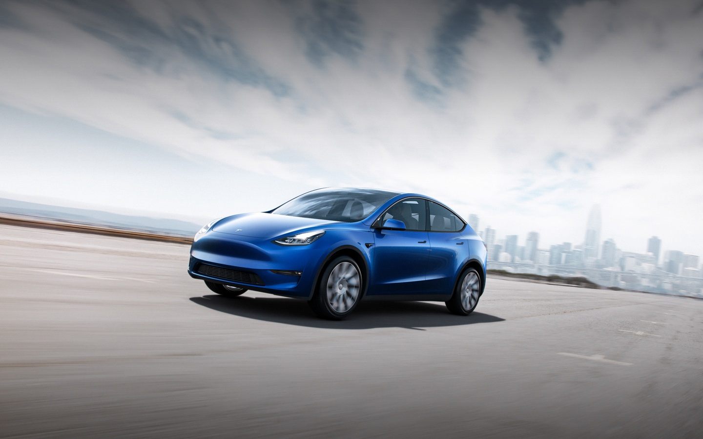 Tesla Model Y 3/4 front driving ny background