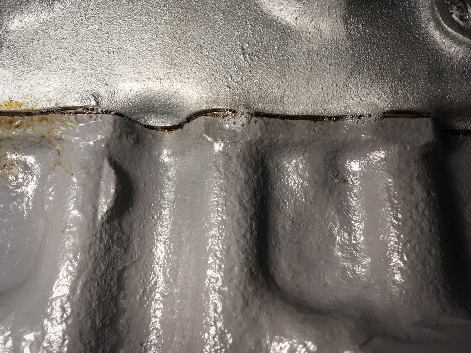 One of several spots where pressure-testing revealed bubbles at the edge of the head gasket.
