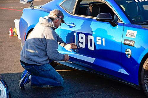SCCA applying door stickers camaro