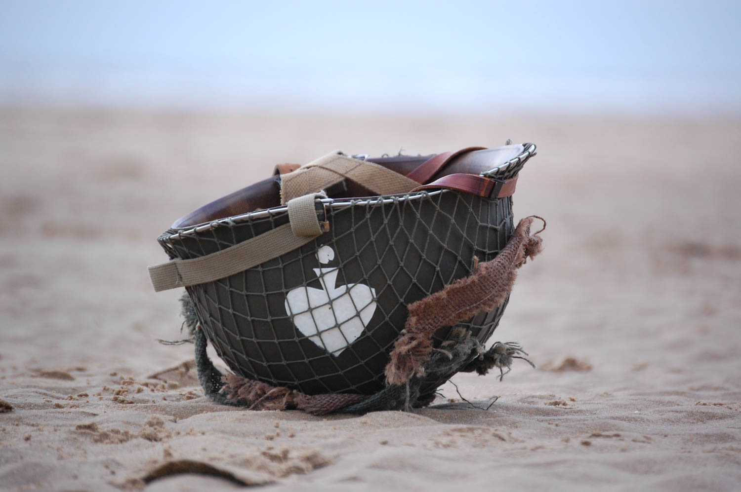 A U.S. Army helmet lies in the sand of Omaha Beach after a reenactment of the 29th Infantry's bloody assault of the beach on D-Day. Today the beach hosts millions of visitors per year interested in its wartime history, as well as hordes of French summer holiday sun-seekers.