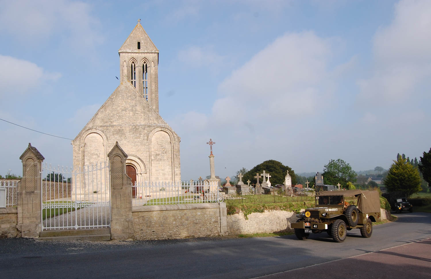 Members of the MVT in a Dodge weapons carrier convoy pass the Eglise Saint-Romain church near Etreham in Normandy, not far from where British and Canadian infantry units landed on D-Day.