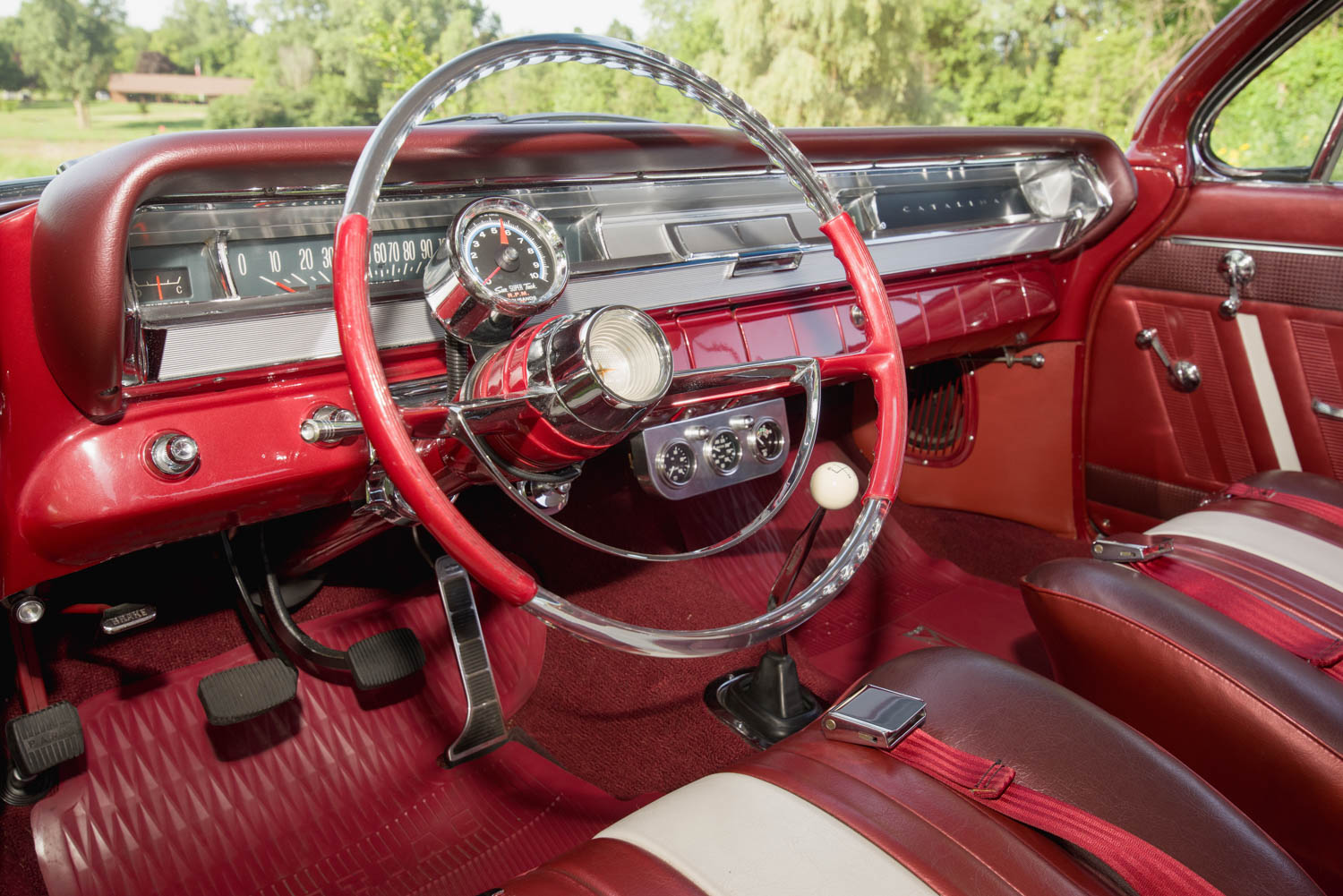 A panel covers the dash opening where the radio would have been on a standard Catalina. Note the tri-color Pontiac Ventura upholstery.