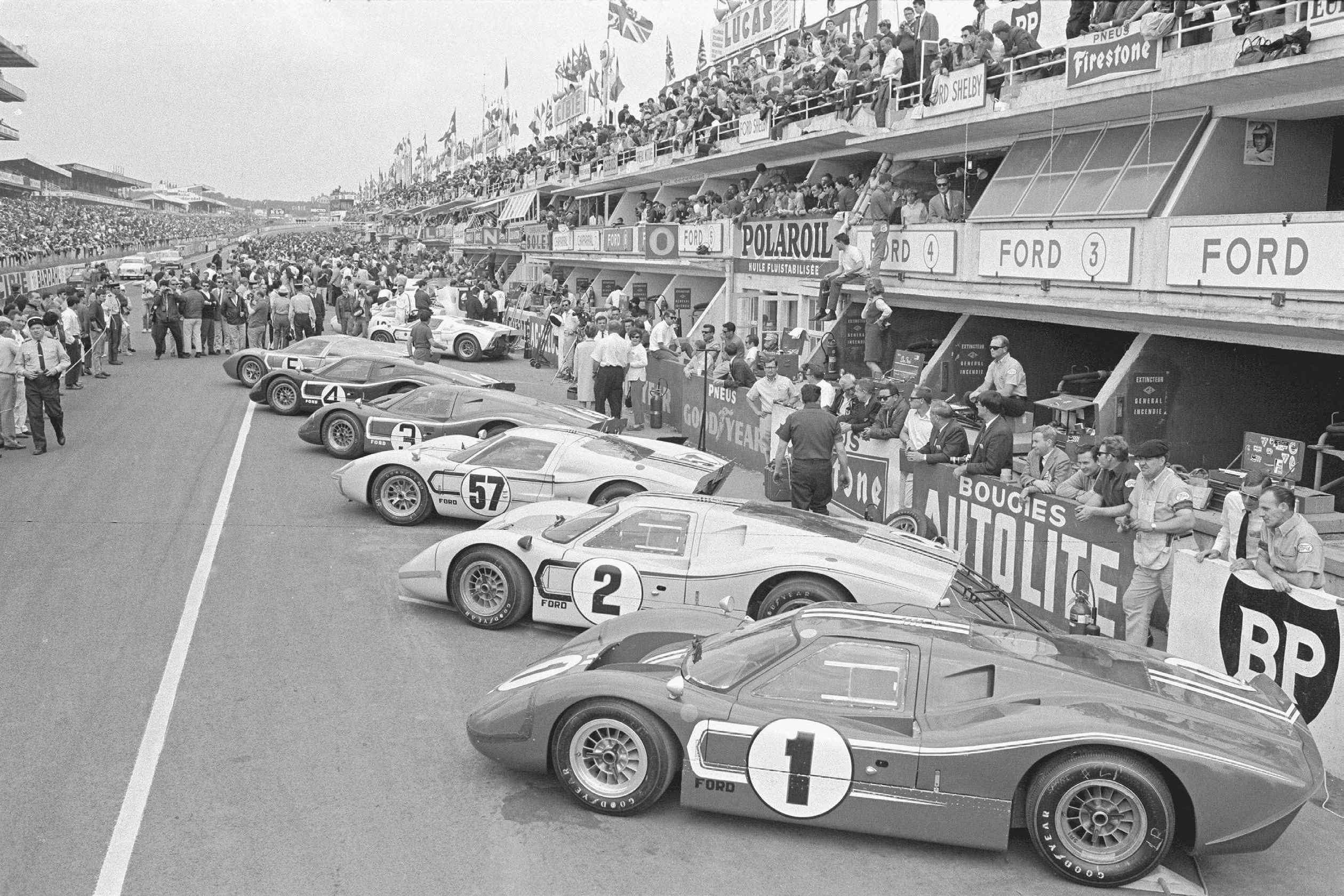 A posed prerace shot shows the Ford armada at Le Mans. The three Shelby entries are Nos. 1, 2, and 57, while Nos. 3, 4, and 5 belong to Holman & Moody. The white Ford France entry, driven by Jo Schlesser and Guy Ligier, is parked just beyond.