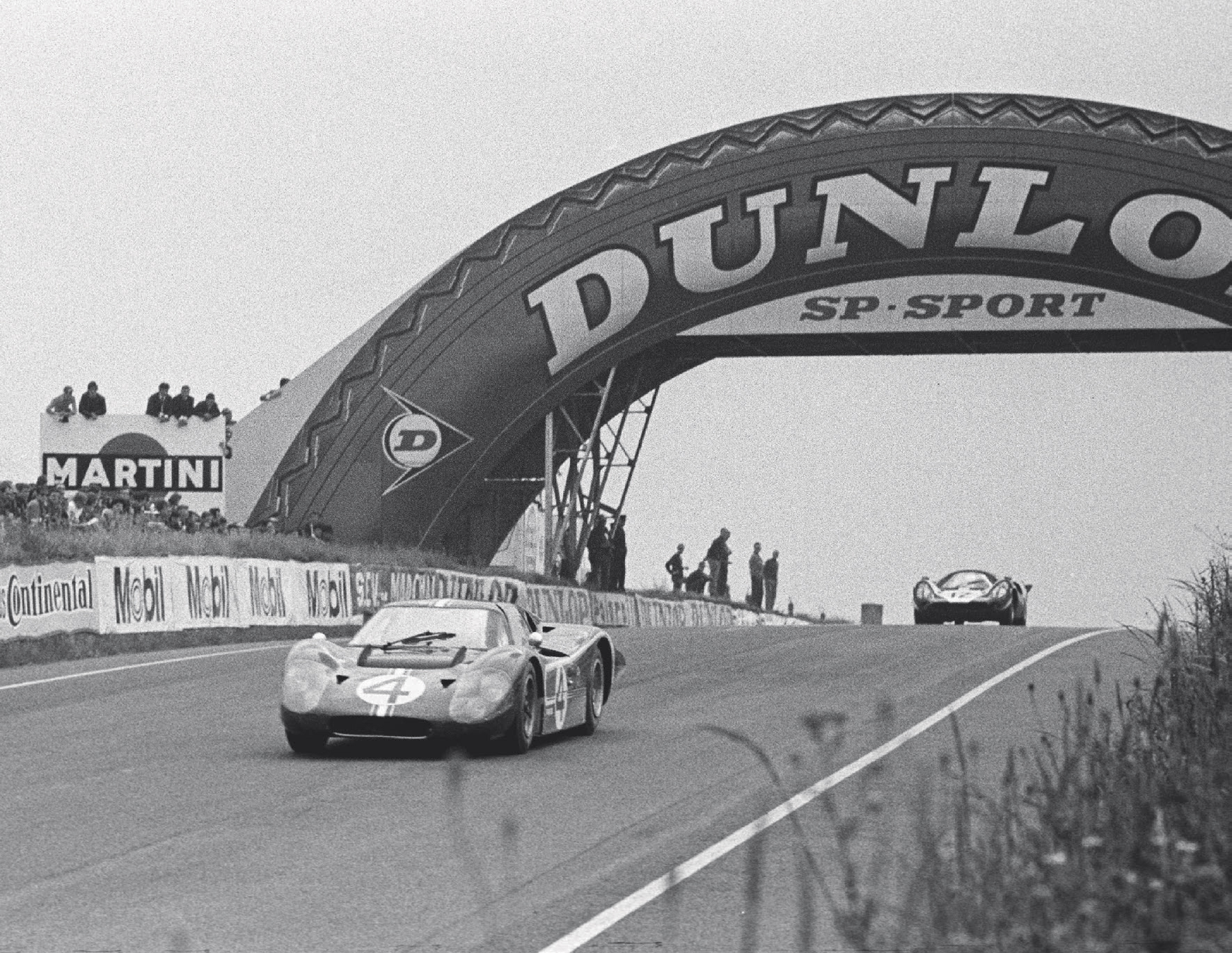 The Holman & Moody Mark IV driven by Denny Hulme and Lloyd Ruby leads a Lola T70 under the Dunlop Bridge. Although Hulme set an early lap record, the car retired when Ruby beached it at Tertre Rouge.