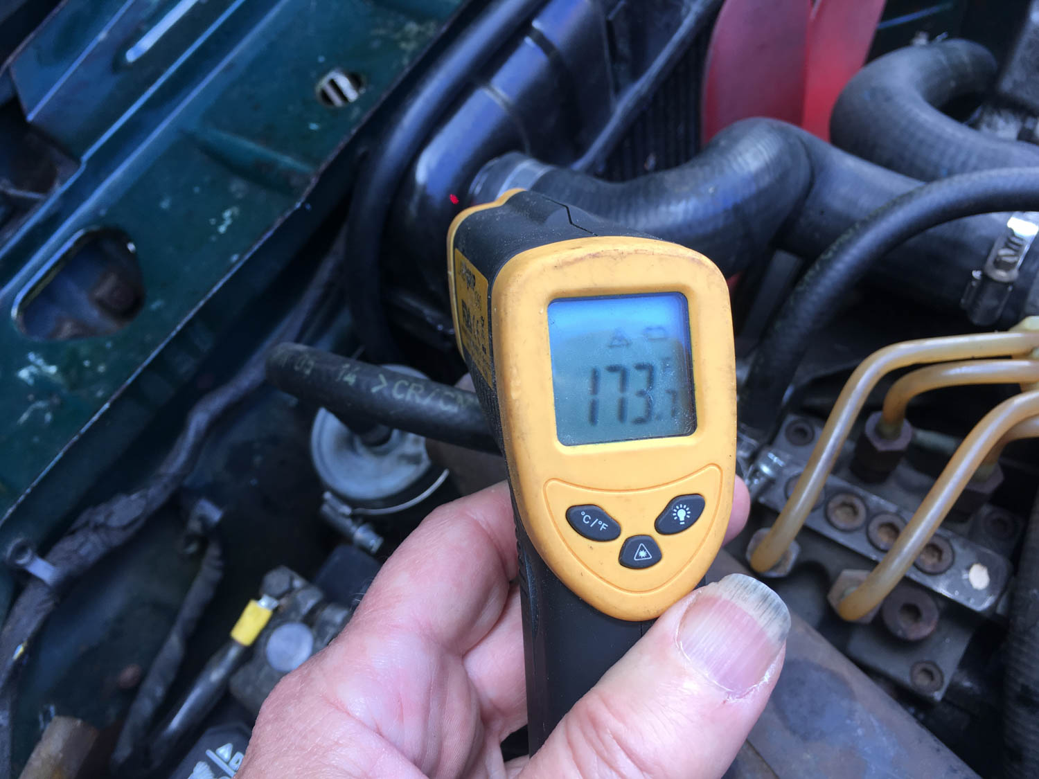 Infrared temperature guns are popular, but you really need to use them before you have trouble in order to get a baseline on what the temperature should be. This is on the upper radiator tank of a barely warmed-up car.