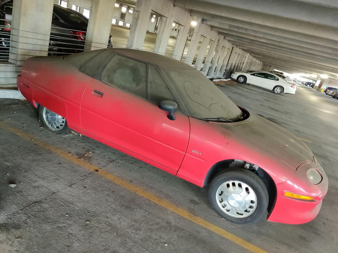 dusty EV1 car in parking garage