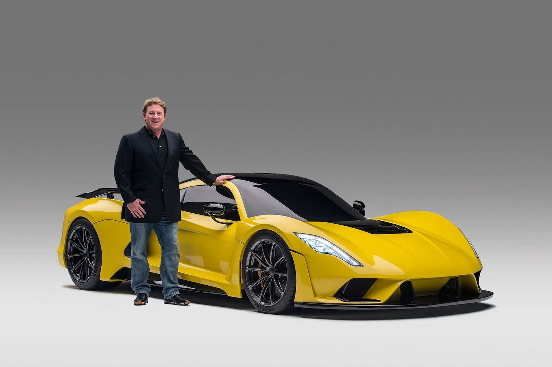 man standing beside yellow venom f5 car front three-quarter