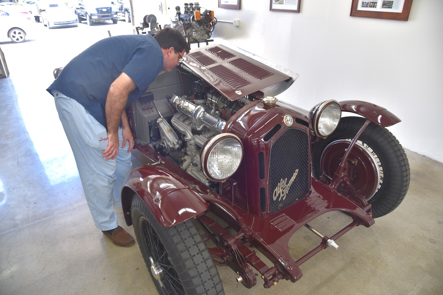 man inspects old alfa romeo engine