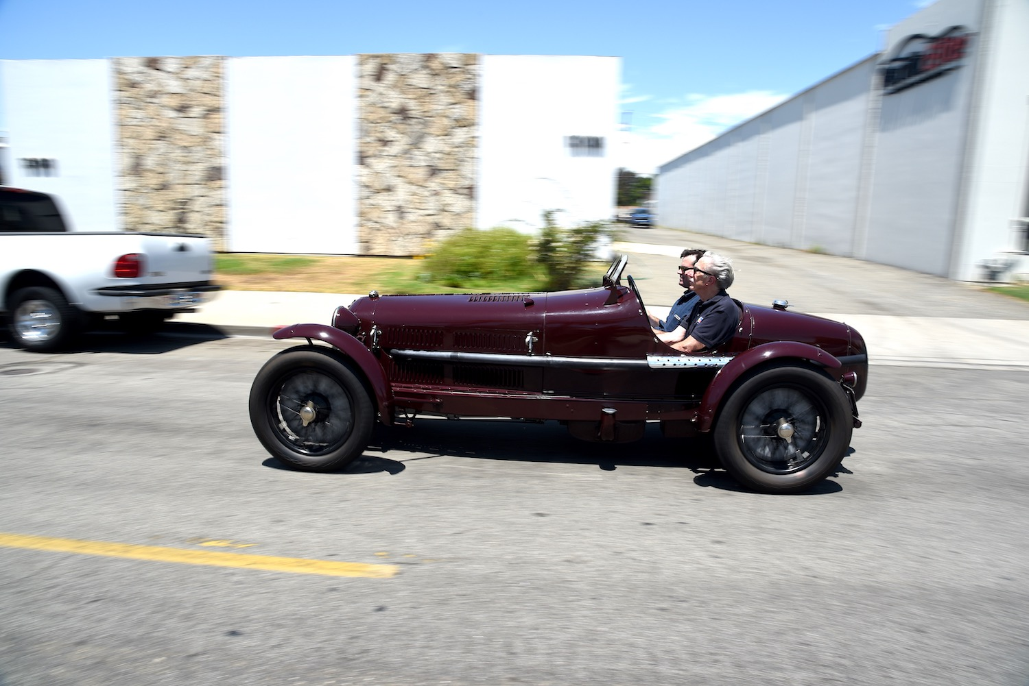 men driving vintage alfa in motion side-view